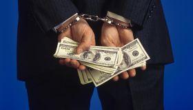Handcuffed businessman holding cash