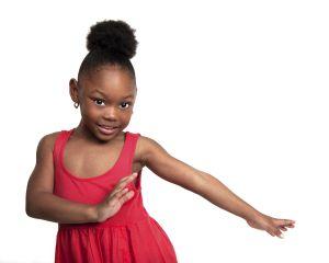 Beautiful little girl wearing red dress dances