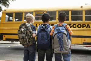 Three boys (8-9) standing with backpacks outdoors near school bus, rear view