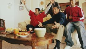 Three generations of men cheering in living room
