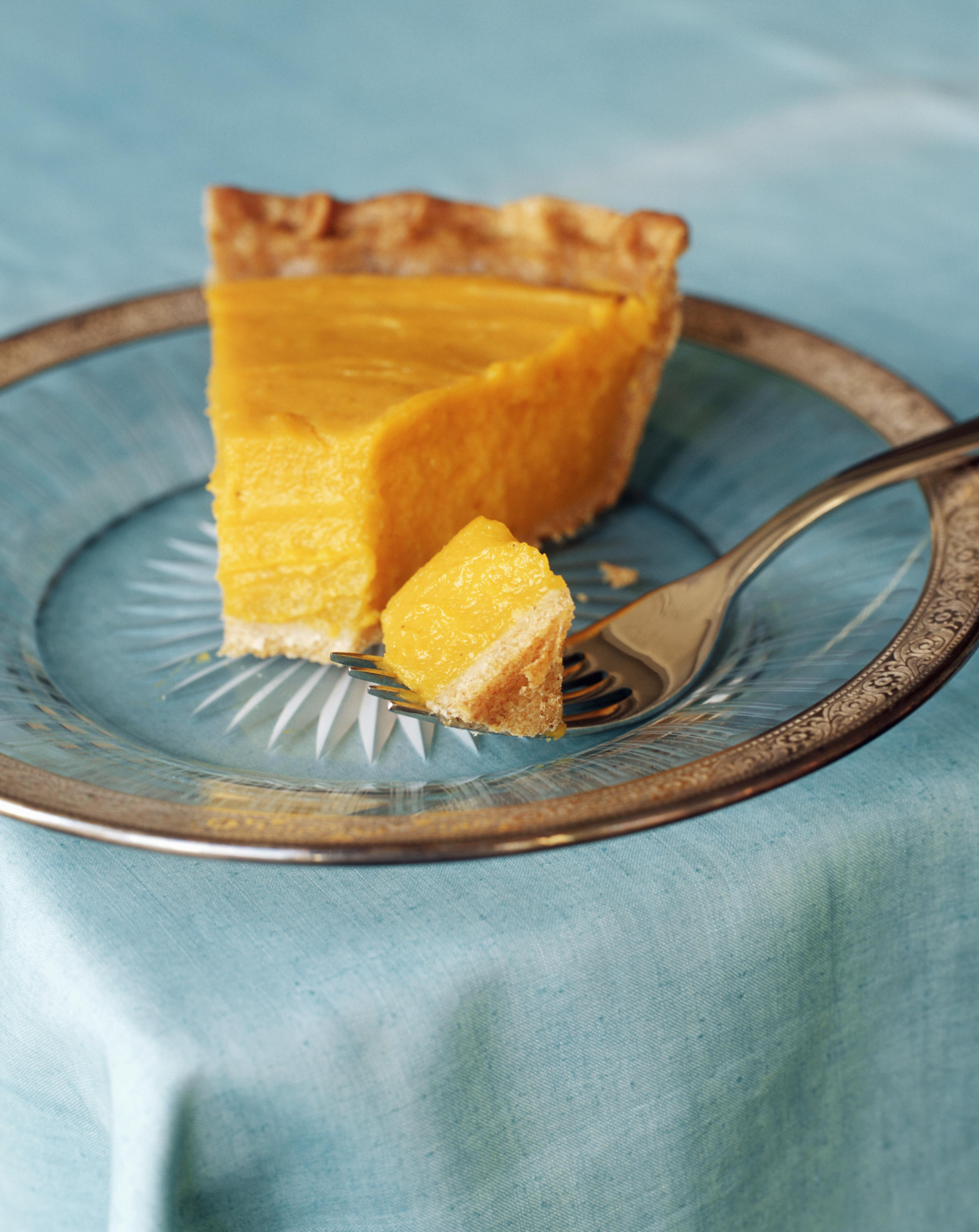 Slice of pumpkin pie with piece on fork, close-up