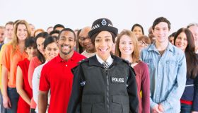 Portrait of smiling policewoman in front of large crowd