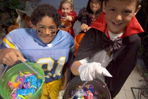Children (4-8) in Halloween costumes trick-or-treating, elevated view