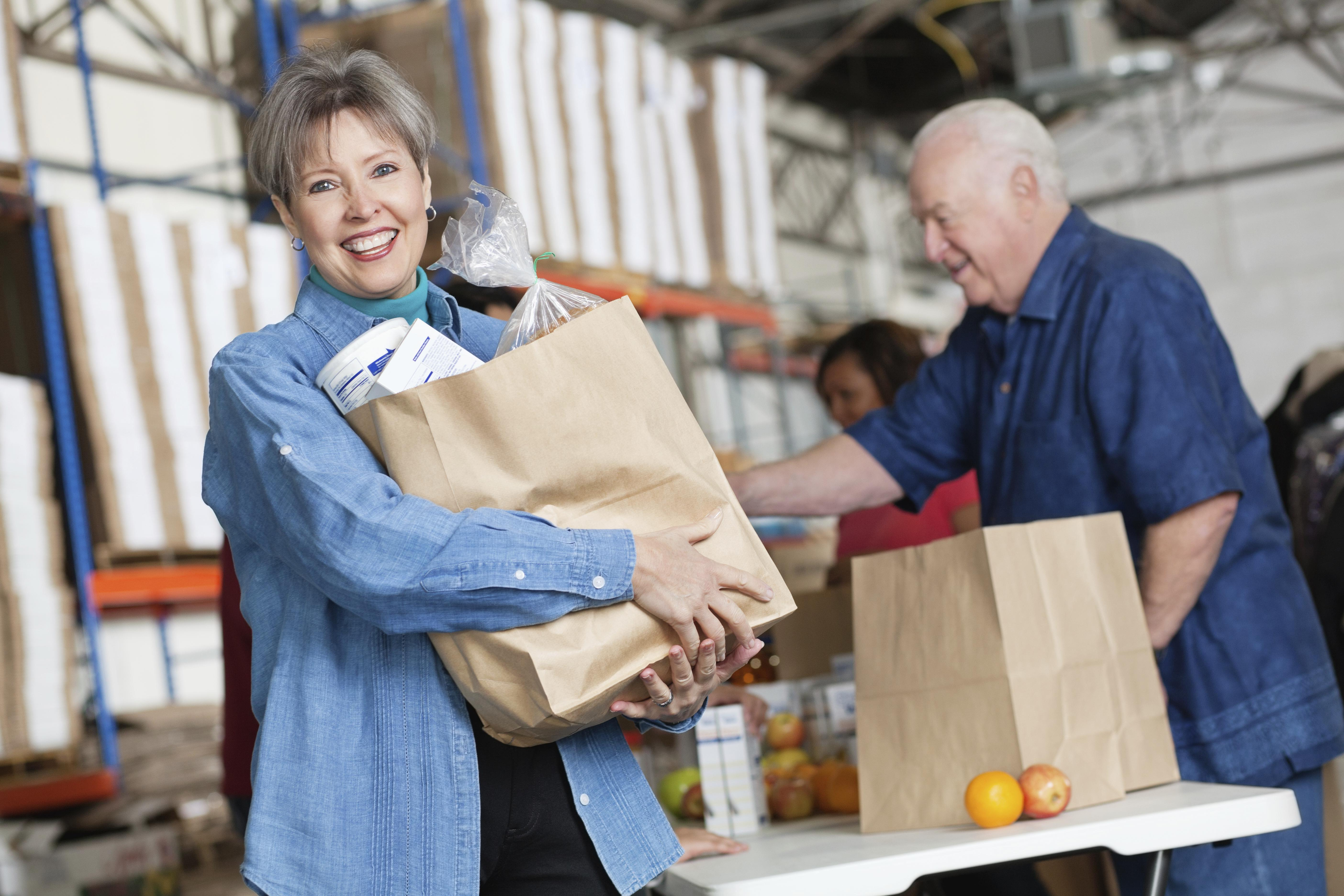 Happy mature woman holding groceries at food pantry