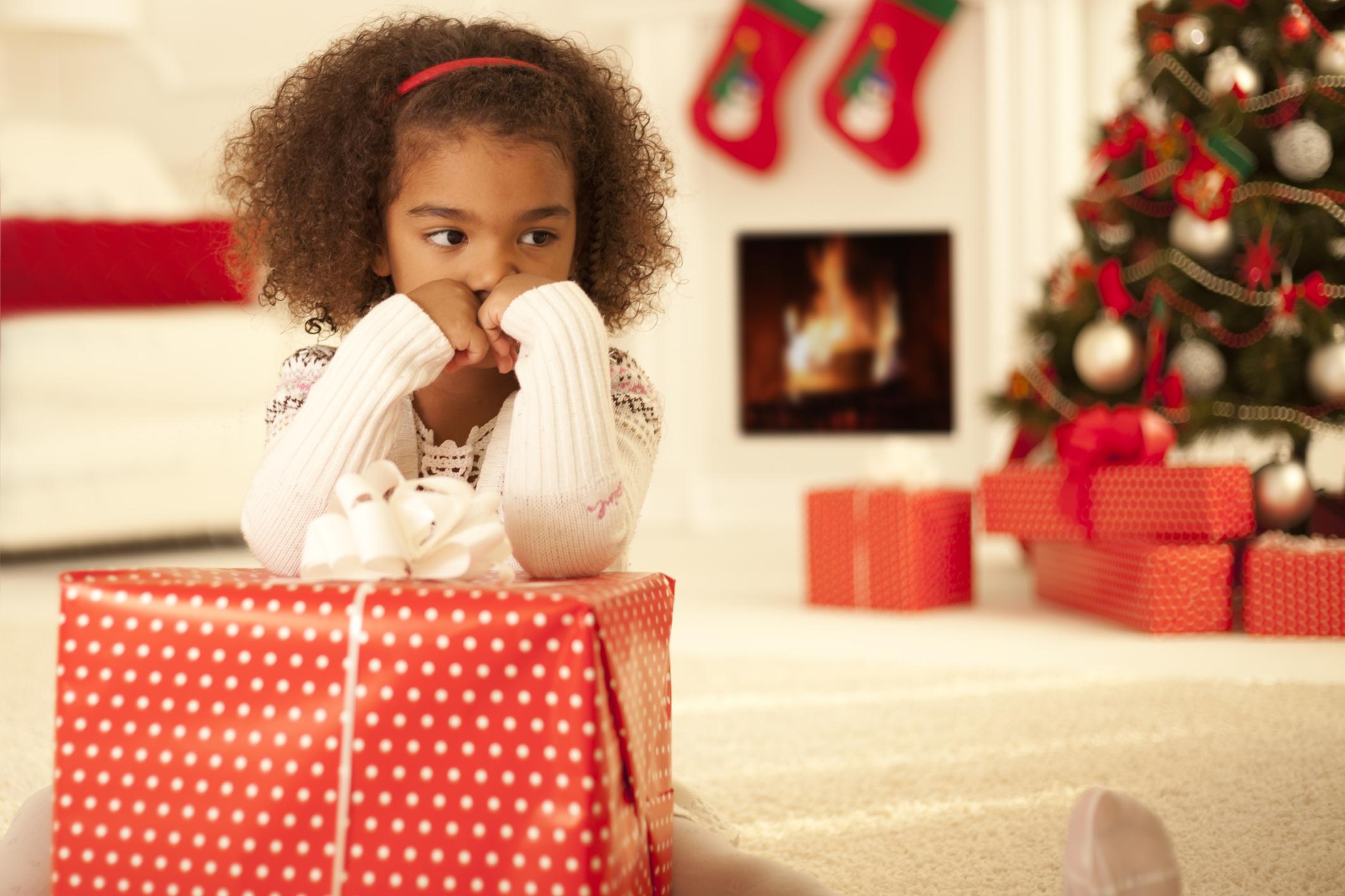 Sad little girl with Christmas present
