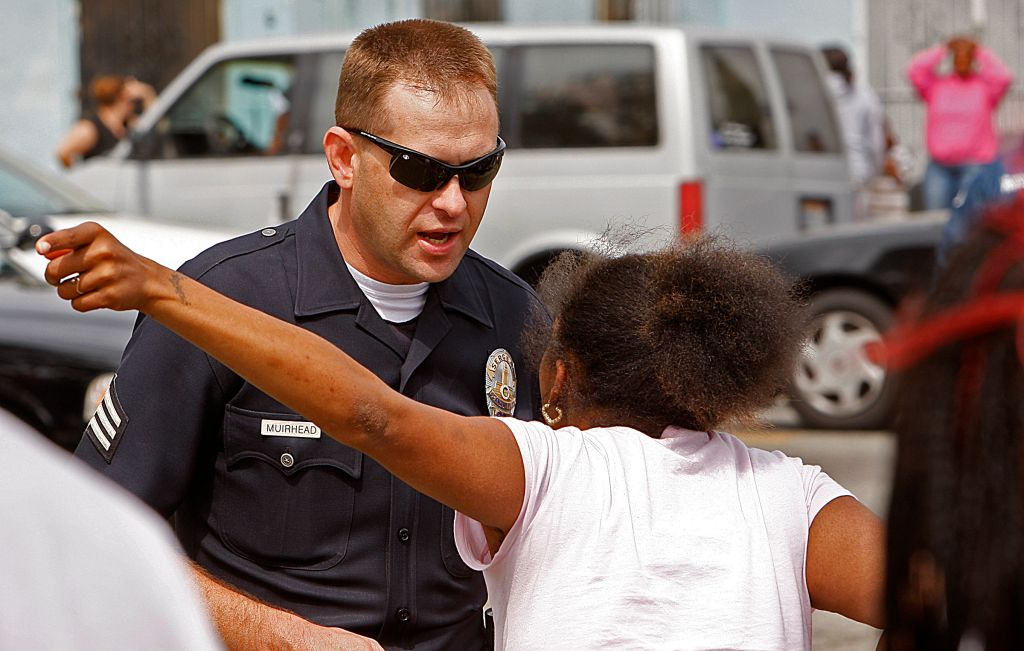 An LAPD officer talks to an irate parent waiting Friday, May 9, 2008, at Locke High School in South