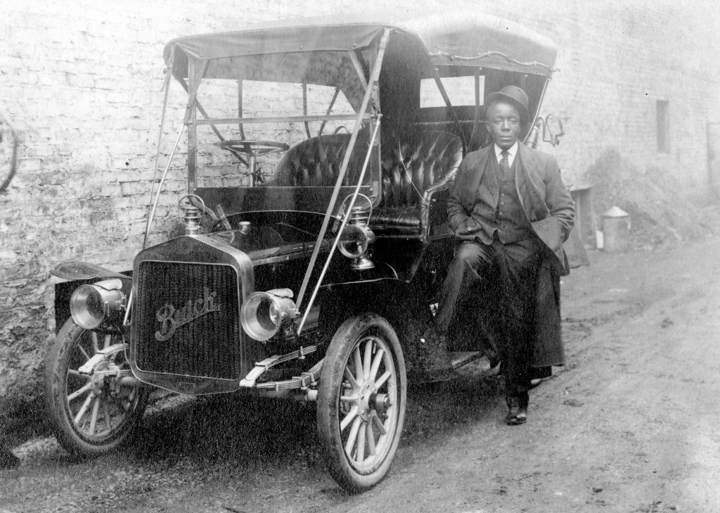 Black Wall Street - Full length shot of African American man leaning against a Buick car parked against a building, wearing a suit and hat tilted on his head, neutral facial expression, 1920.