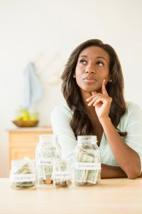 Black woman putting money into savings jars