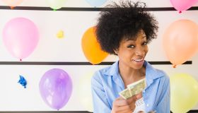 African American woman counting money at balloon wall