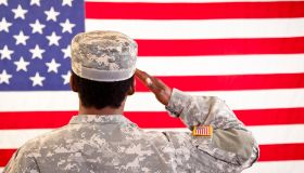 African descent woman in military uniform saluting American flag.