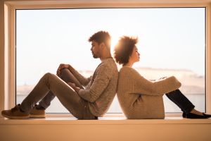 African American couple sitting back to back on a window sill while having relationship difficulties.