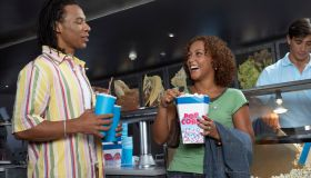 Couple Buying Popcorn and Soda at Movie Theater
