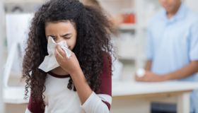 African American preteen girl uses tissue in pharmacy
