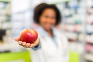 African American pharmacist holding apple in a pharmacy.