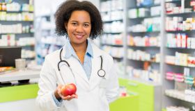 African American pharmacist holding apple and looking at camera.