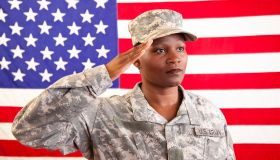 African descent female in military uniform saluting American flag