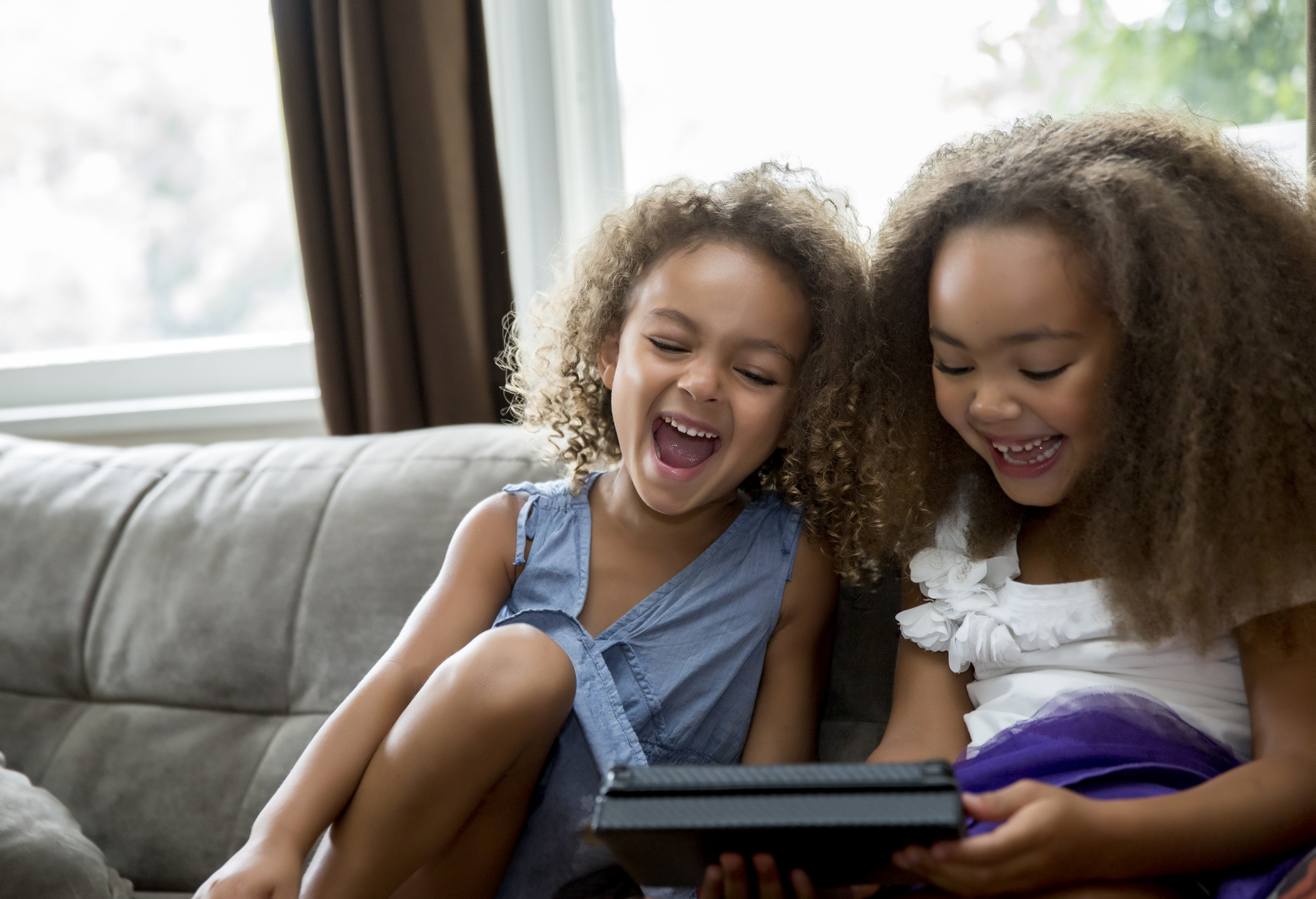 Mixed race girls using digital tablet on sofa