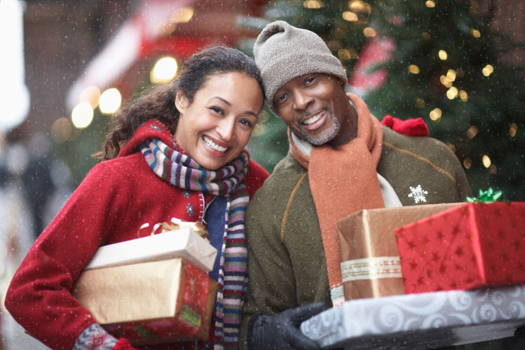 Couple with Christmas presents on street, portrait