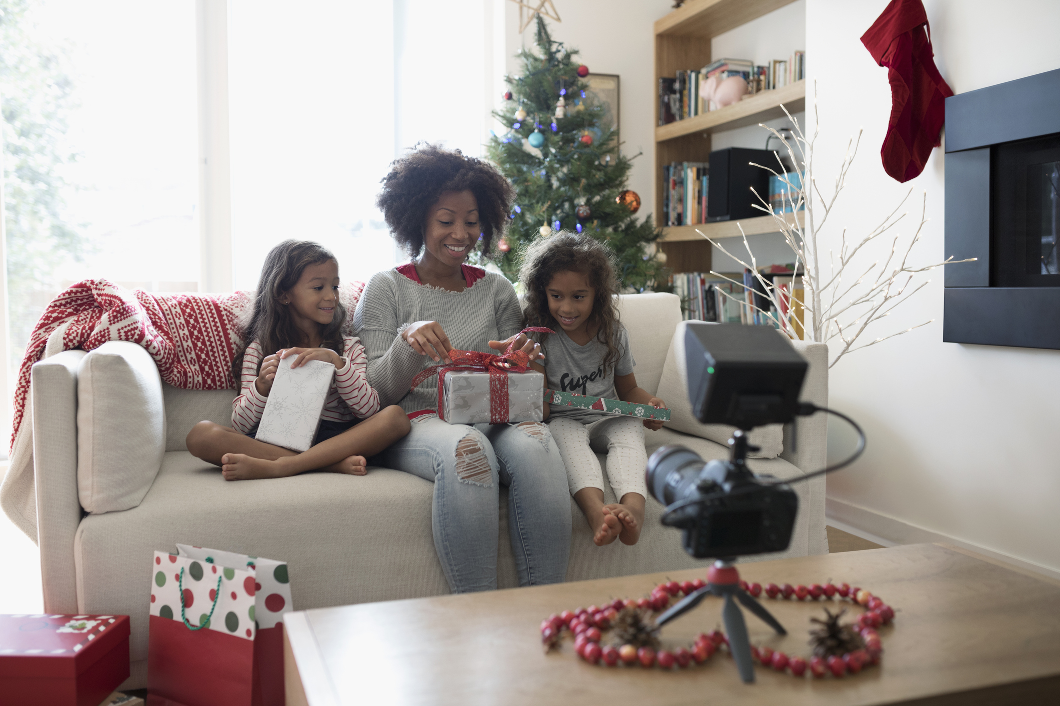 Mother and daughters opening Christmas gifts for video camera in living room