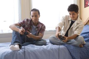 Two teenage boys (16-17) playing video games on bed