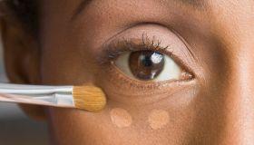 African American woman applying makeup