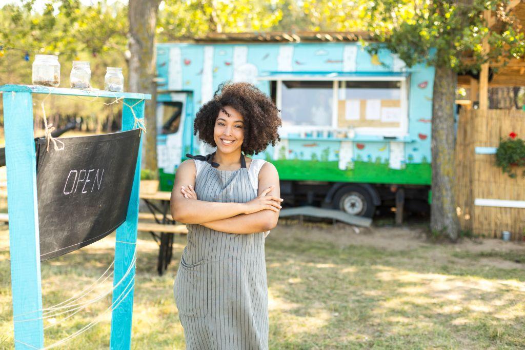 Food van owner posing next to signboard