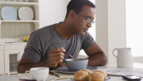 USA, California, Los Angeles, Mature man eating breakfast and reading newspaper