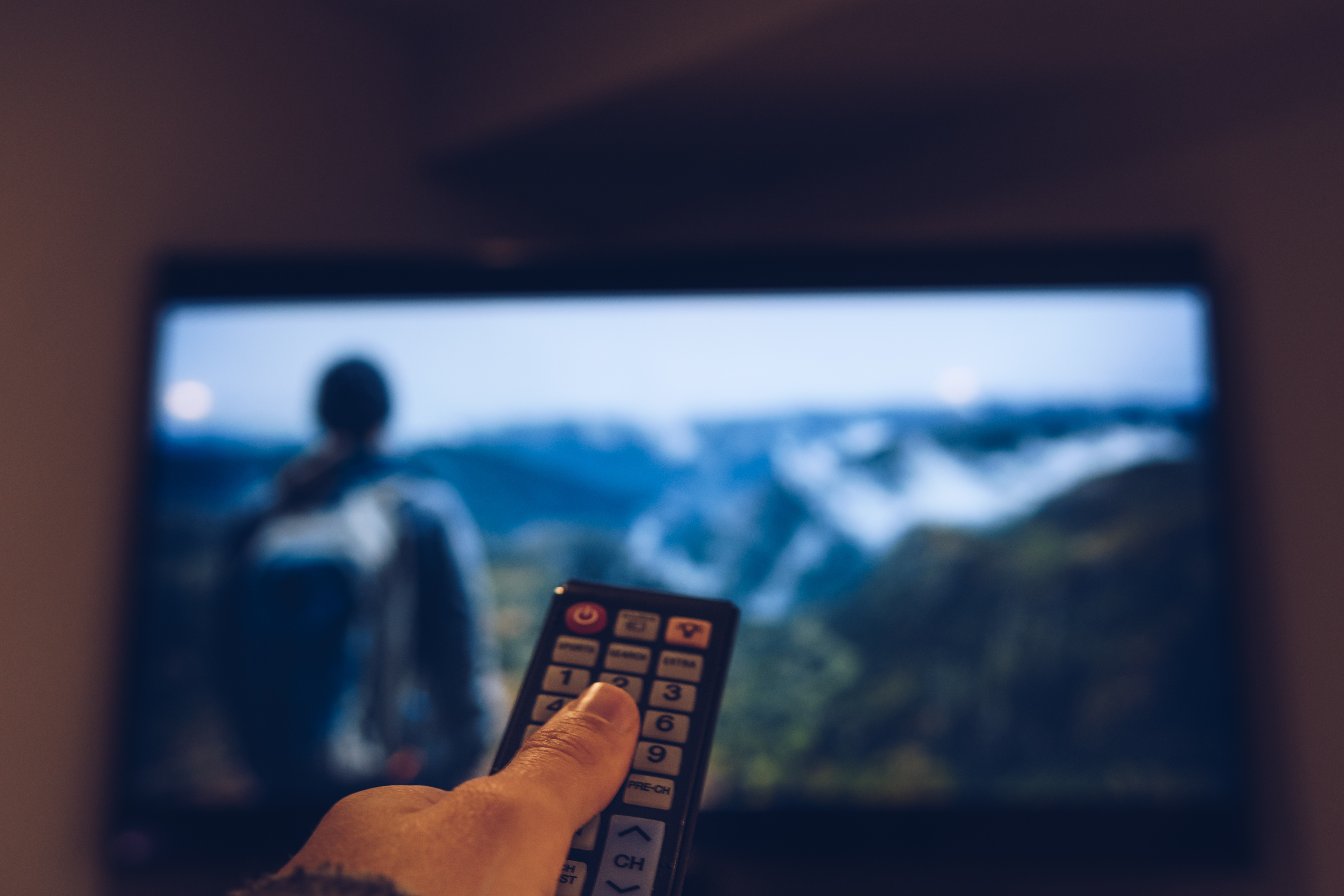 Cropped Image Of Hand Holding Remote Control In Front Of Television Set