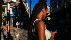Young afro french woman wearing african braids standing on...