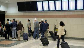 Passengers with rolling luggage at Hartsfield-Jackson Atlanta International Airport.