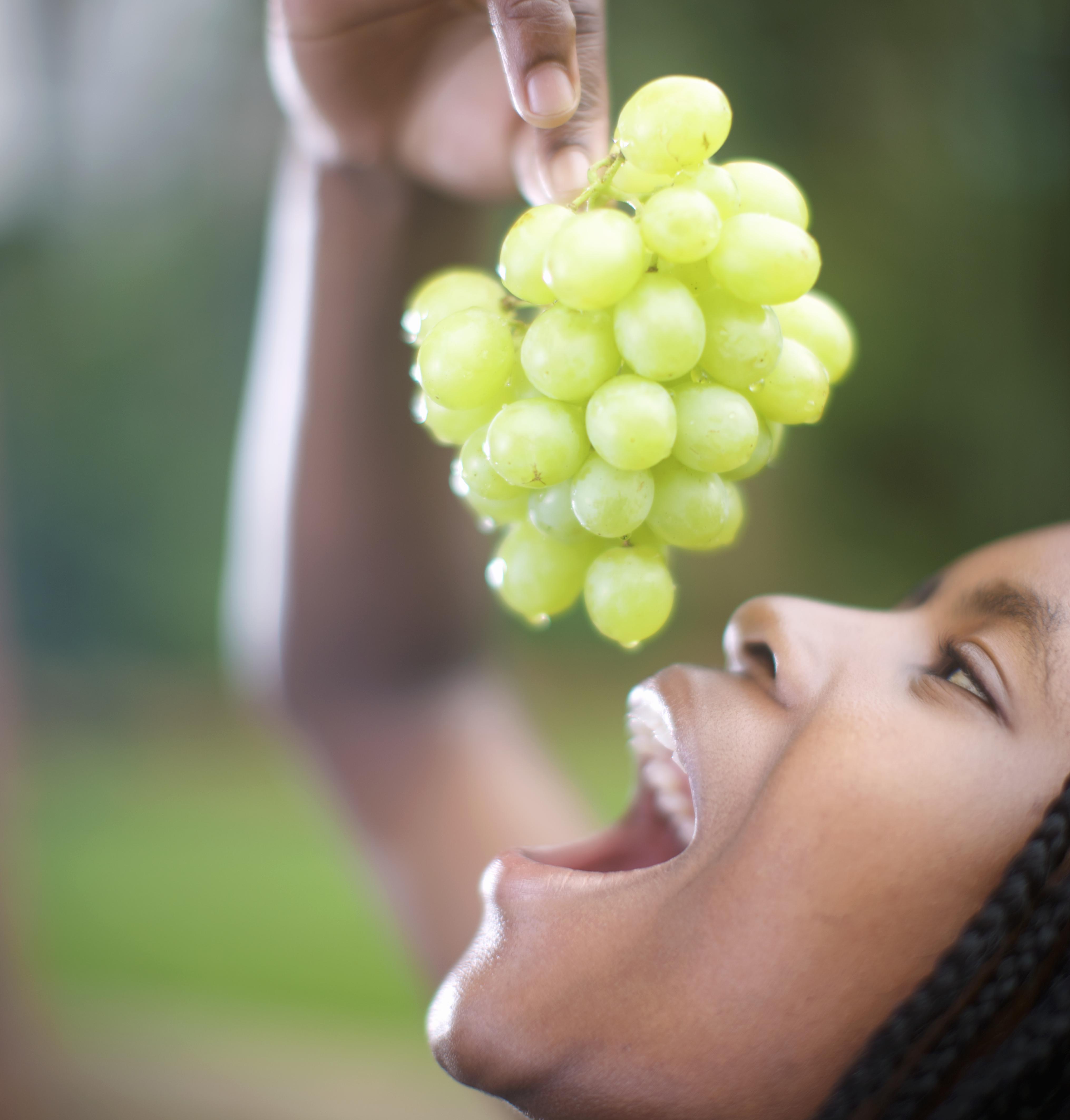Woman eating grapes, Pietermaritzburg, KwaZulu-Natal Province, South Africa