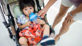 Toddler girl drinking water in stroller