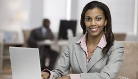 Mixed race businesswoman using laptop at desk
