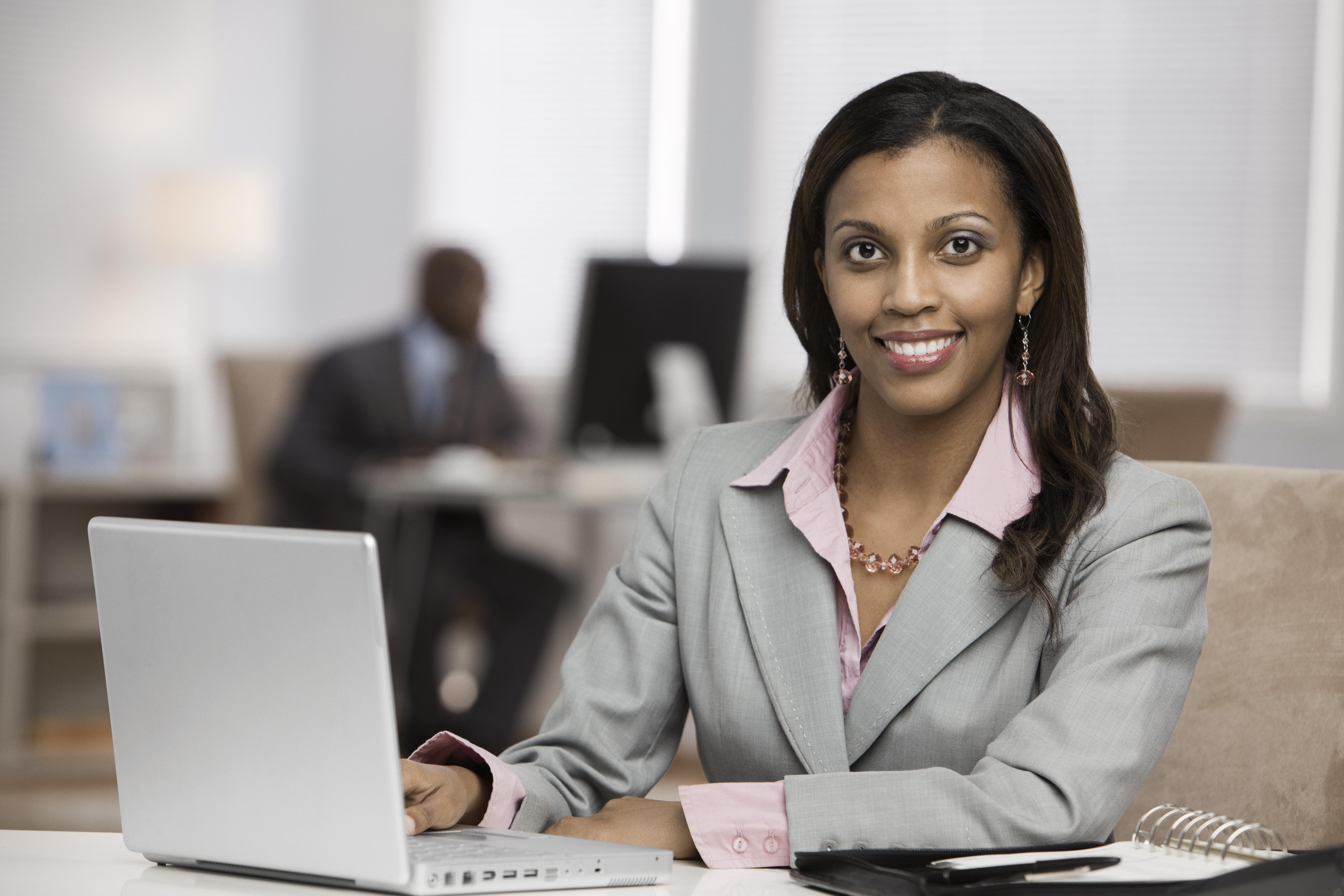 Mixed race businesswoman using laptop at desk