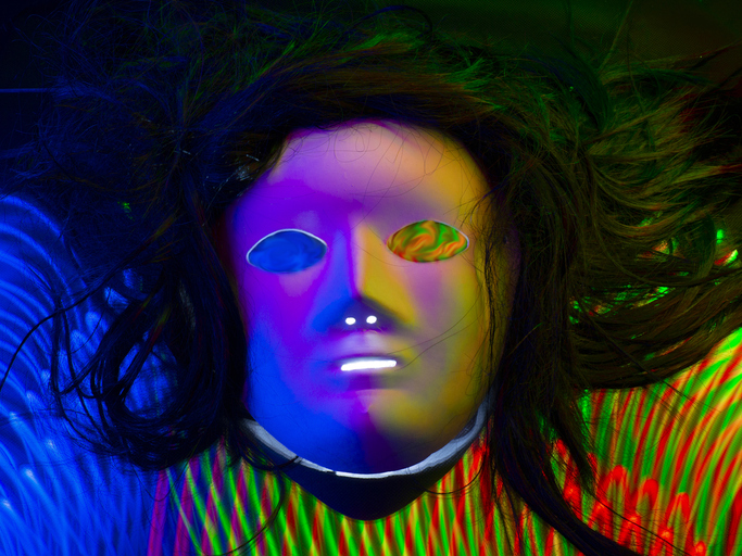 Mask with hair on digital green-red and blue lines forming a lattice in 3D. Light painting