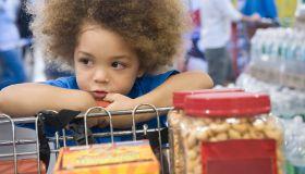Mixed race boy sitting in shopping cart
