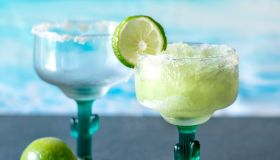 A Frozen Margarita With An Empty Glass Behind And Slices Of Limes For A Garnish