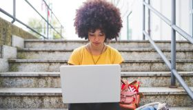 Young woman with afro hairdo using laptop on stairs in the city