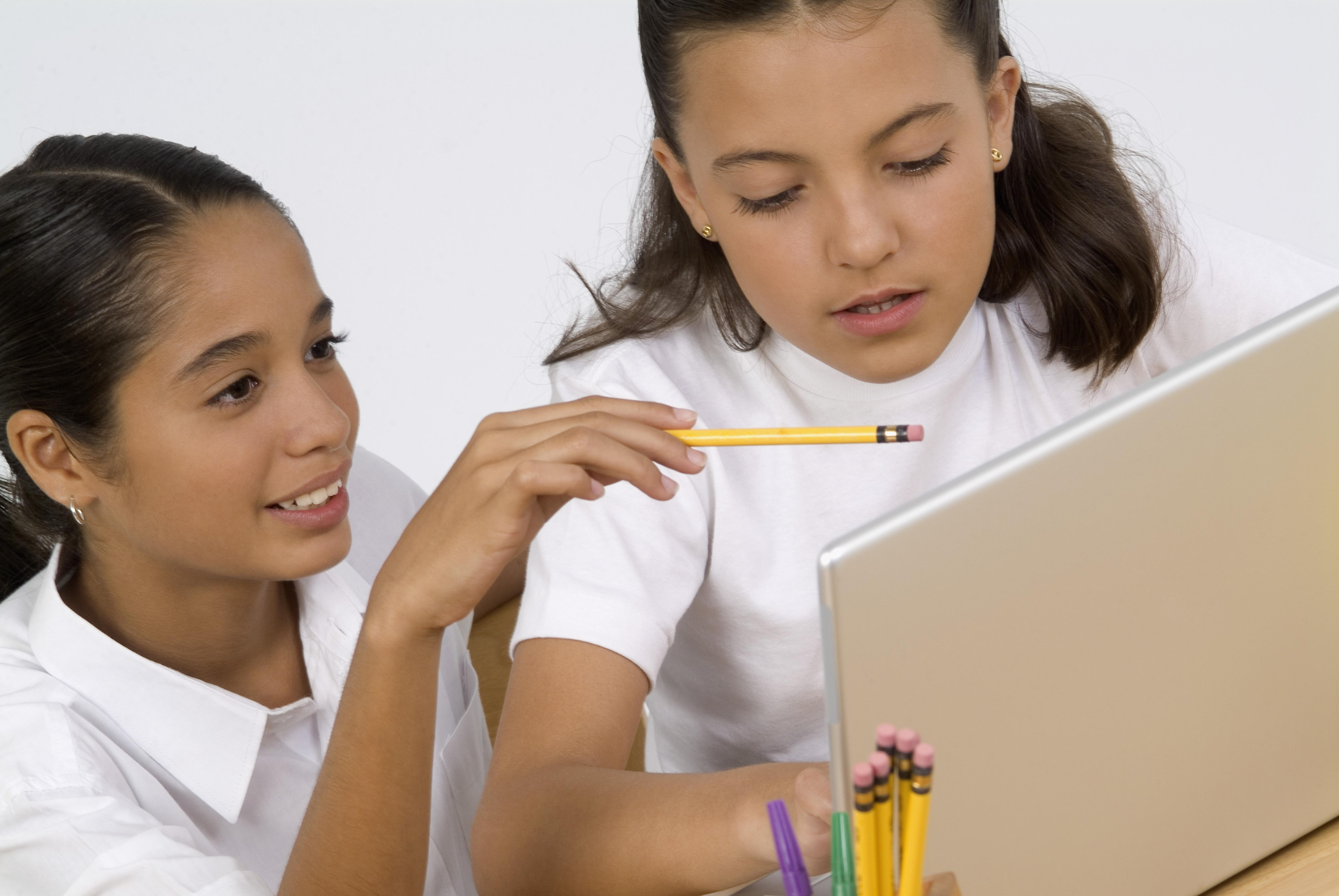 Two girls studying with laptop computer, close-up