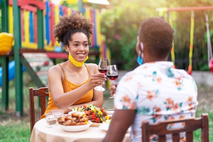Afro Couple wearing protective face mask having staycation romantic dinner on back yard, during COVID-19