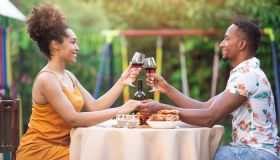 Afro Couple having staycation romantic dinner on back yard, during COVID-19