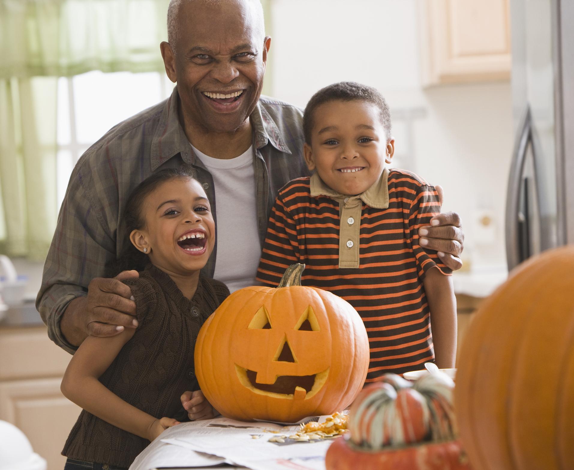 Grandfather and grandchildren carving a pumpkin