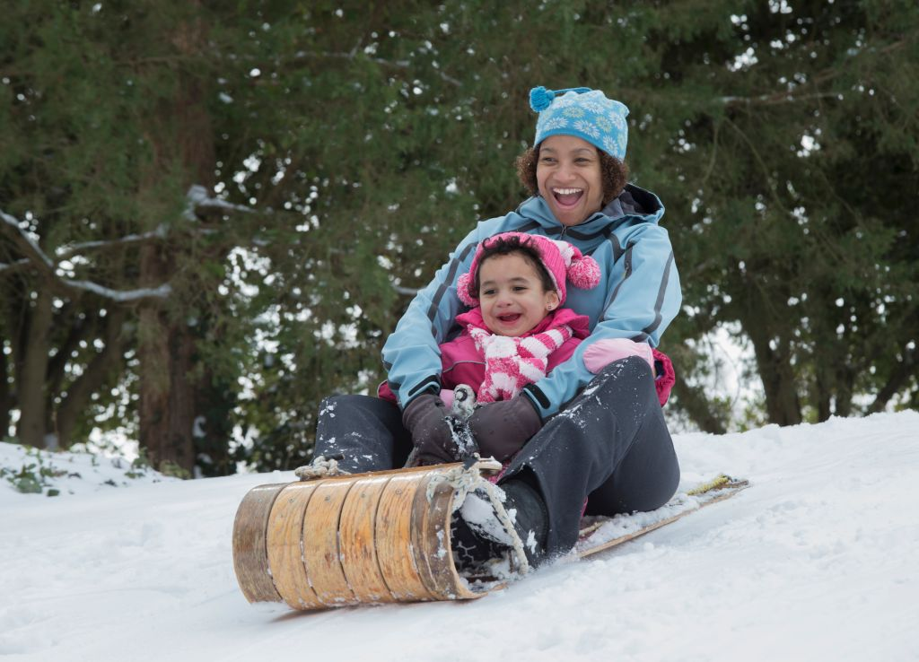 Mother and daughter sledding on snowy hill outdoors