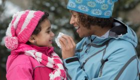 Mother wiping daughter's nose in snow outdoors