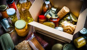 Cardboard box filled with non-perishable foods on wooden table. High angle view.