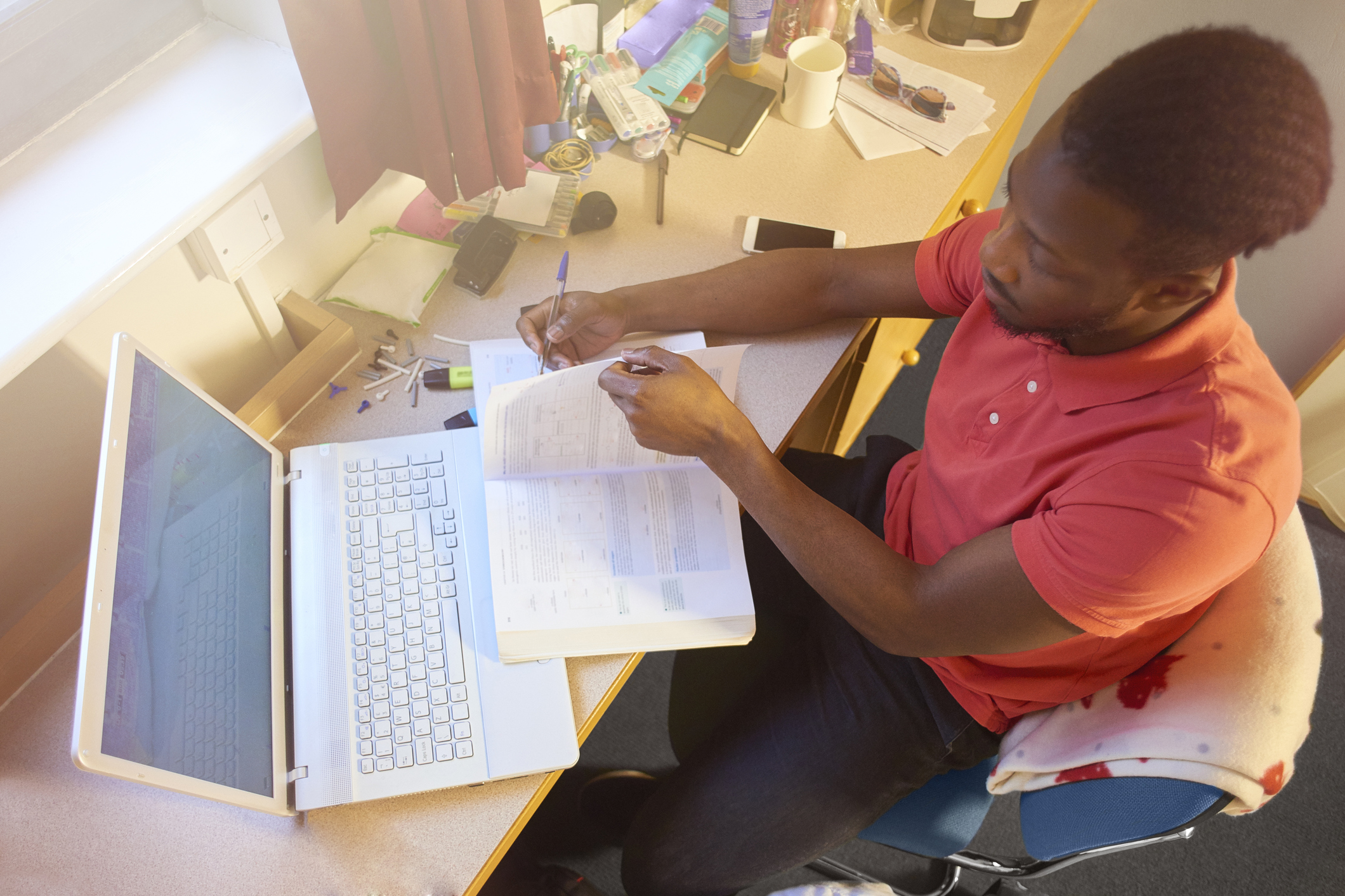 Male university student studying in his room at uni