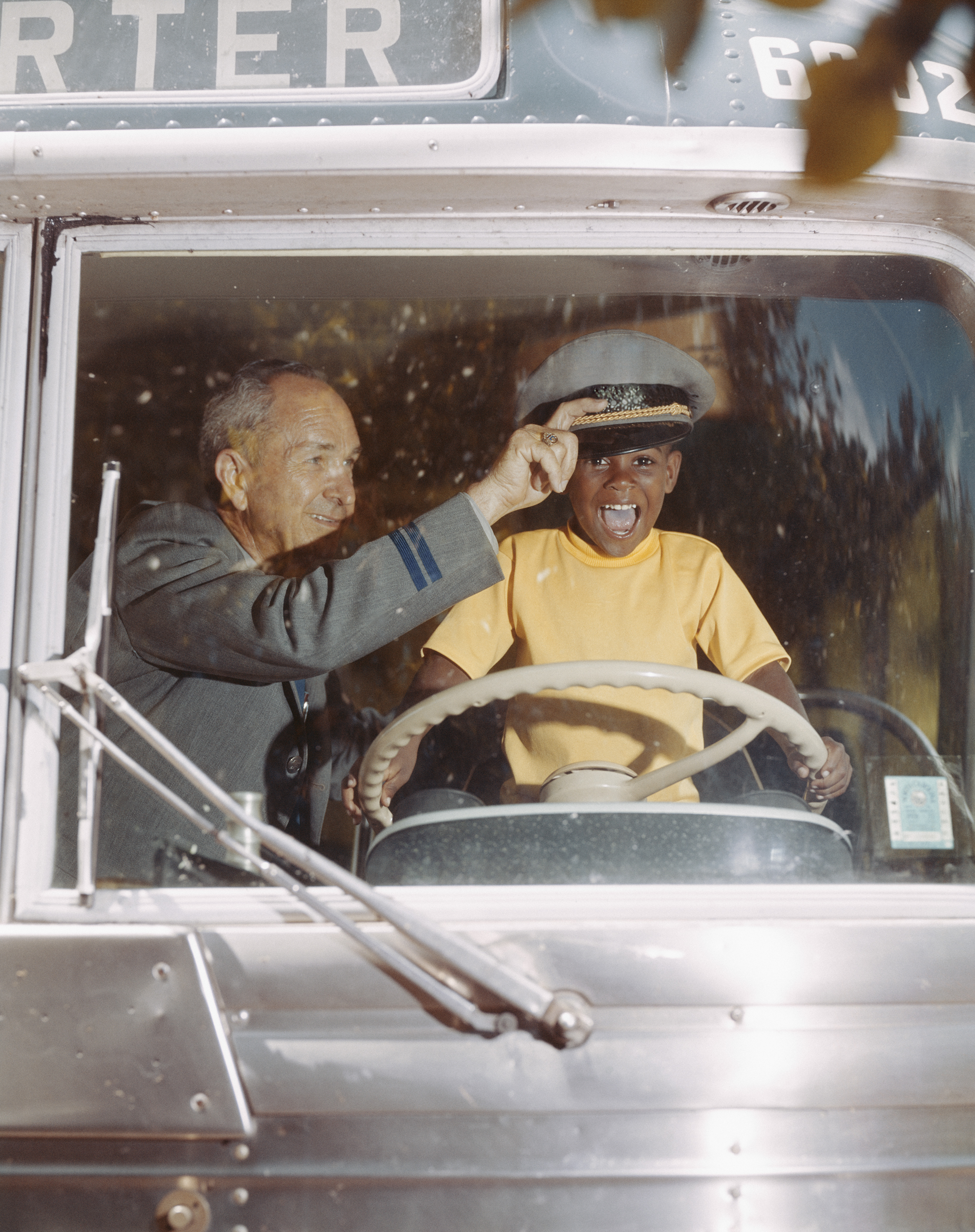 Bus driver giving hat to happy boy holding steering wheel