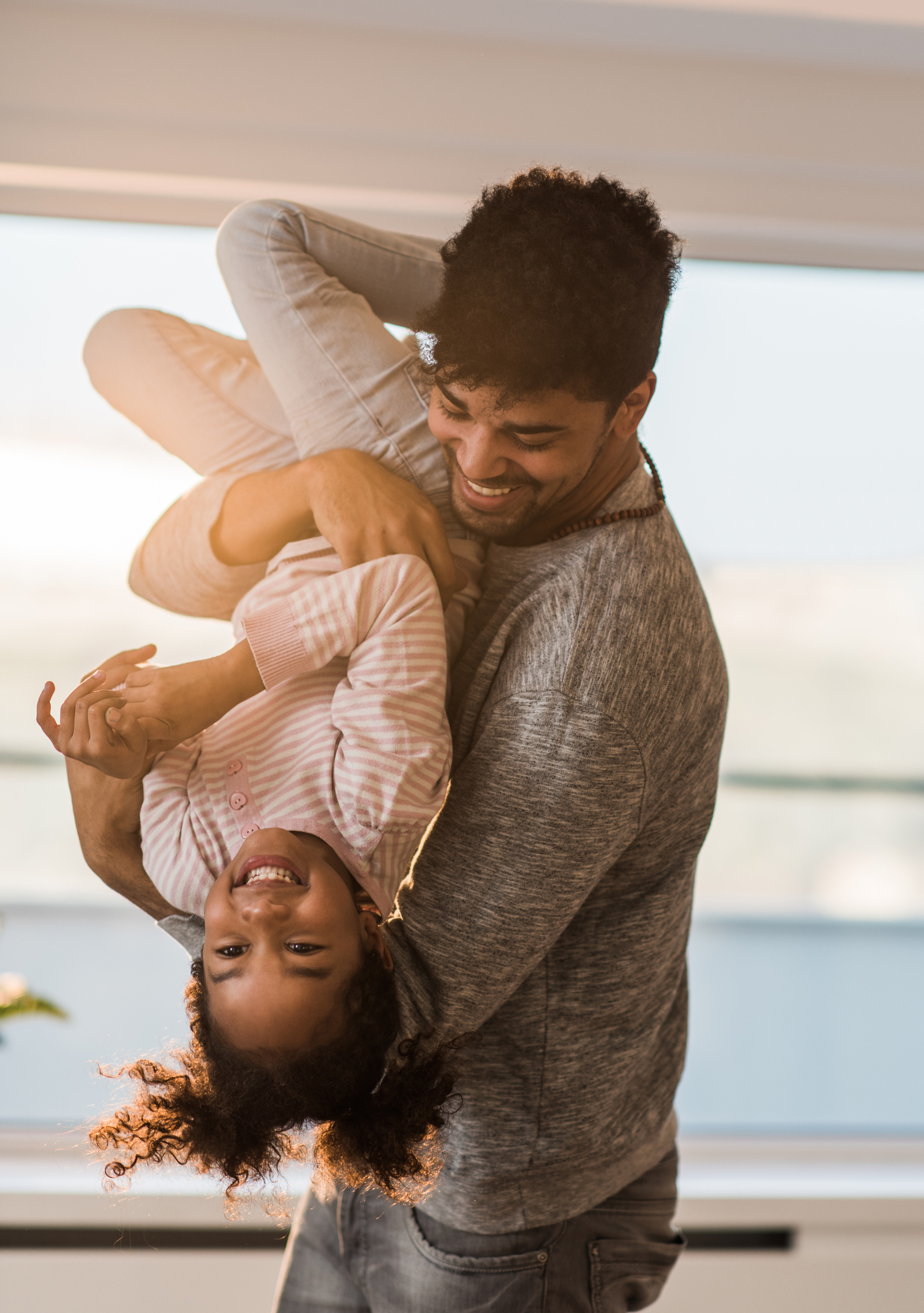 Young black father having fun while playing with his daughter at home.
