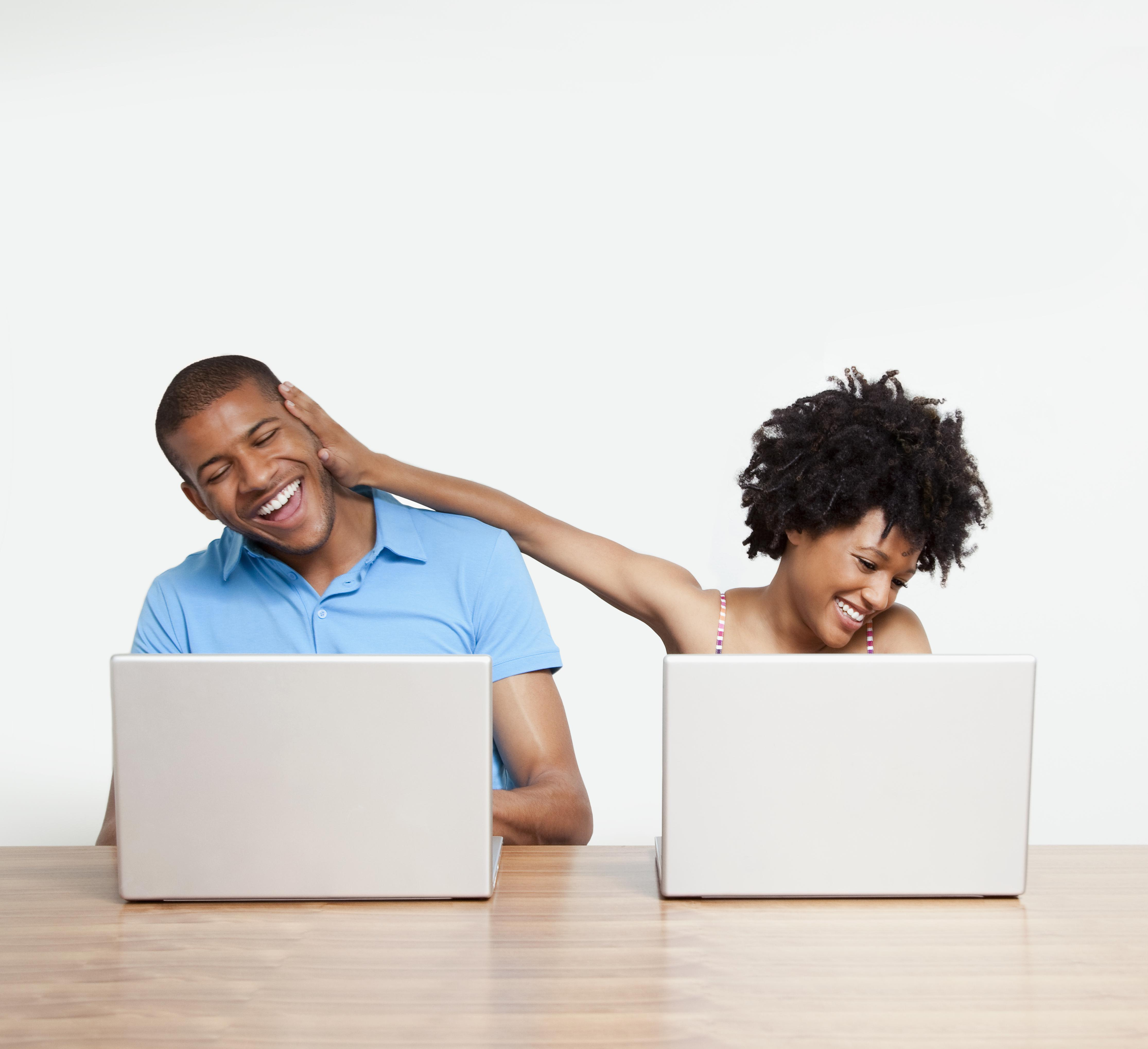 Woman joking with man as they work on laptops