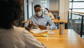 Businesspeople wearing masks in the office during COVID-19 pandemic